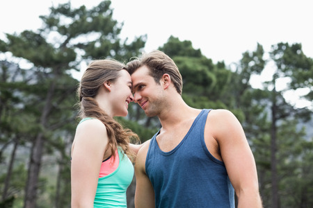 causal clothing: Low angle view of young couple couple standing against trees at forest
