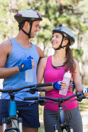 causal clothing: Happy couple holding water bottles while riding bicycle at forest