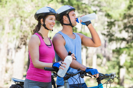 causal clothing: Young couple holding water bottle while riding bicycle at forest Stock Photo