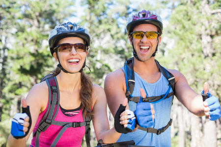 causal: Portrait of happy young couple showing thumbs up sign at forest Stock Photo