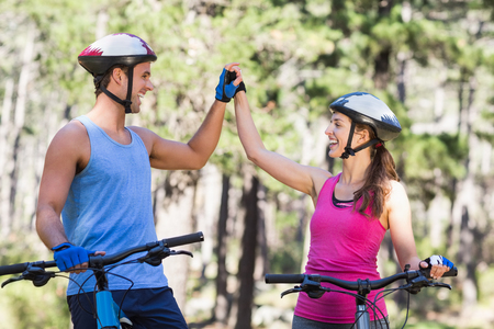 causal clothing: Young couple holding hands while riding bicycle at forest