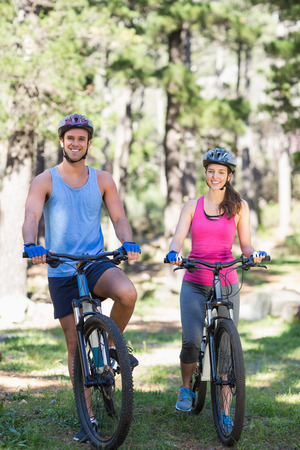 causal clothing: Portrait of smiling young couple with bicycles at forest
