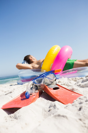 lilo: Man lying on lilo wearing rubber ring on the beach Stock Photo