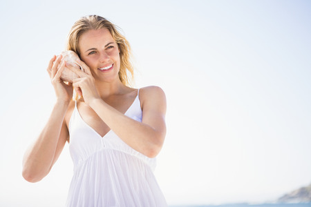 maxi dress: Woman listening into a seashell on the beach
