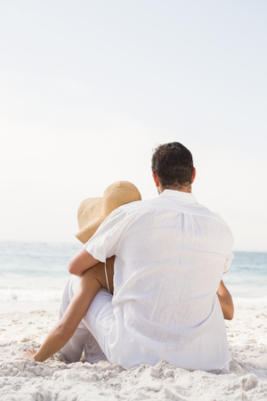 maxi dress: Couple sitting on sand at the beach on a sunny day Stock Photo