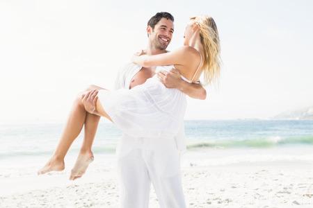 maxi dress: Boyfriend carrying girlfriend on the beach on a sunny day