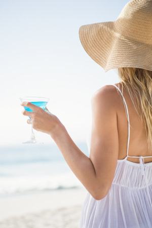 maxi dress: Blonde woman drinking cocktail on the beach