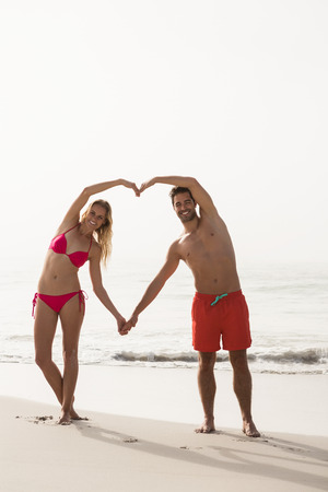 forming: Couple forming a heart with arms on the beach