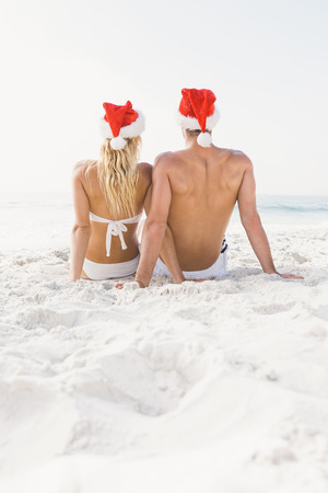 wearing santa hat: Couple wearing santa hat on the beach on a sunny day Stock Photo