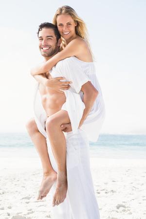 maxi dress: Boyfriend giving piggy back to girlfriend at the beach Stock Photo