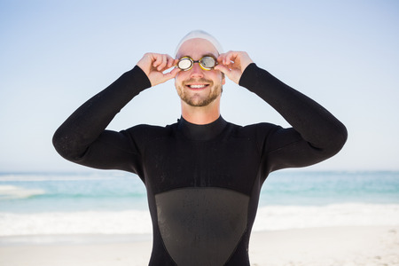 swimming cap: Handsome man wearing swimming cap and goggles on the beach Stock Photo