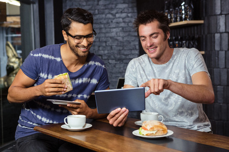 Friends using a tablet while eating sandwiches in a coffee shop