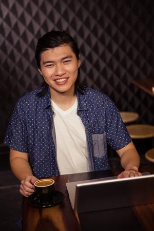 sho: Man using a laptop in a coffee sho