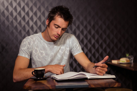clothes organizer: Hipster having coffee and writing in planner in coffee shop Stock Photo