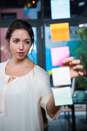 sticky note: Businesswoman looking at sticky note in office Stock Photo