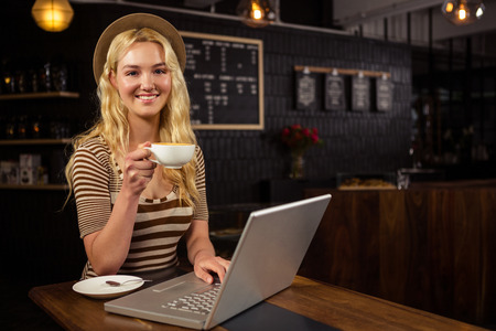 food shop: Woman drinking coffee and using laptop at coffee shop