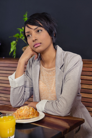 miserable: Unhappy woman sitting with breakfast in a coffee shop