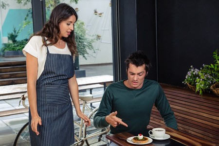 order in: Angry client quarreling with waitress about wrong order in coffee shop Stock Photo