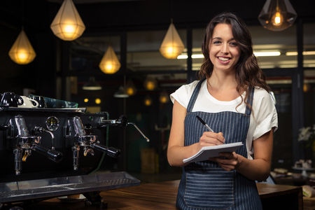 noting: Pretty barista taking notes near coffee machine in coffee shop
