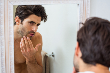 stubble: Man looking in mirror and checking his stubble in bathroom