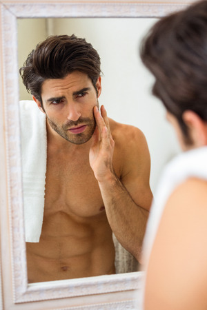 domiciles: Man looking in mirror and checking his skin in bathroom