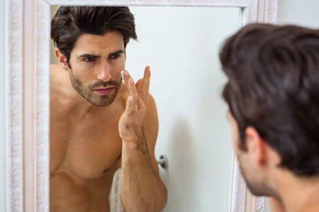 domicile: Man in bathroom applying moisturizer on his face