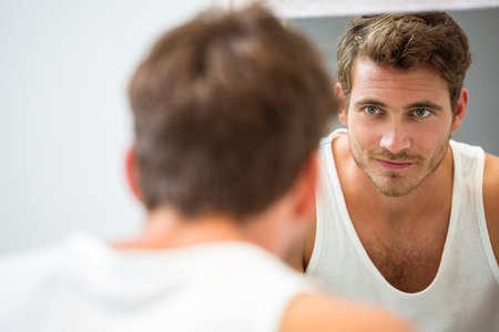 mirror: Smart young man looking at himself in mirror at bathroom