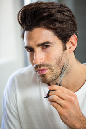domiciles: Close-up of young man cutting beard with scissor in bathroom