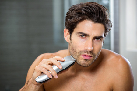 trimmer: Portrait of young man shaving with trimmer in bathroom
