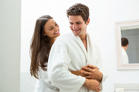 couple bathroom: Happy couple in bathrobe embracing each other in bathroom Stock Photo