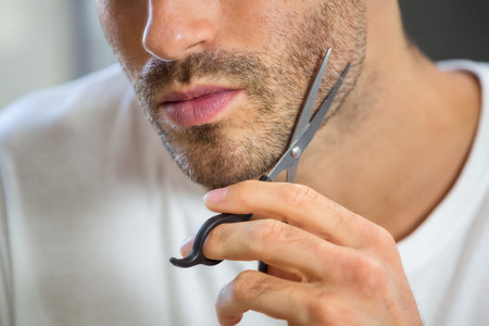 body grooming: Close-up of young man cutting beard with scissor in bathroom