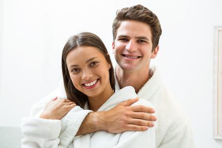 couple bathroom: Portrait of happy couple in bathrobe embracing in the bathroom