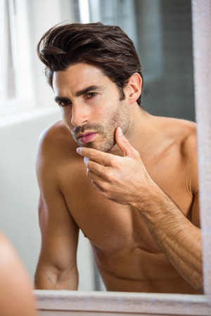 stubble: Reflection of young man checking his stubble in bathroom mirror Stock Photo