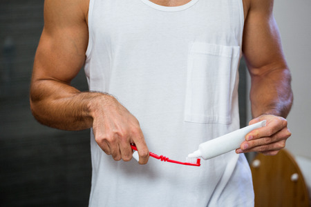 squeezing: Close-up of man squeezing toothpaste on toothbrush