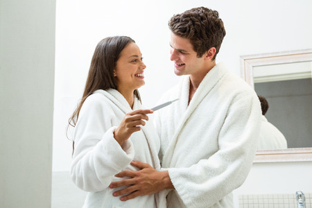 pregnancy test: par feliz que controla la prueba de embarazo en el baño Foto de archivo