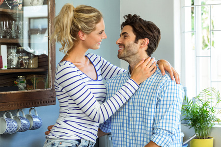 each other: Romantic couple embracing each other in kitchen Stock Photo