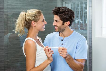 test de grossesse: Happy couple checking pregnancy test in bathroom