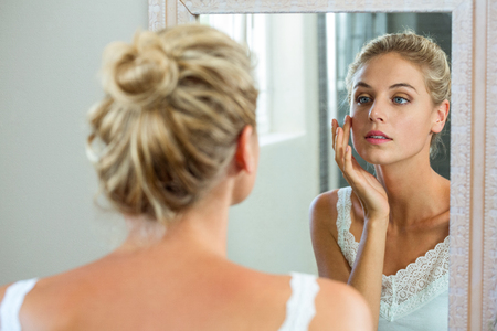 mirror: Reflection of woman checking her skin in bathroom mirror
