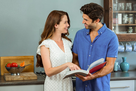 recipe book: Young couple reading recipe book together in kitchen at home