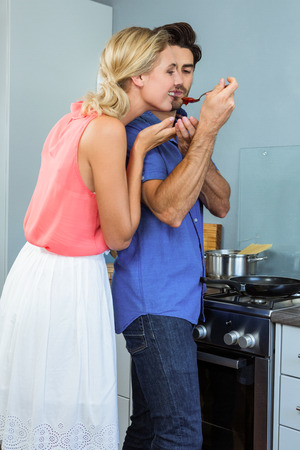 letting: Man letting woman taste a sauce with a spoon in kitchen at home Stock Photo