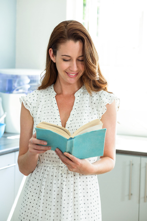 woman reading: Smiling young woman reading book in kitchen at home Stock Photo