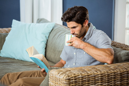 middleaged: Young man having coffee while reading book in living room