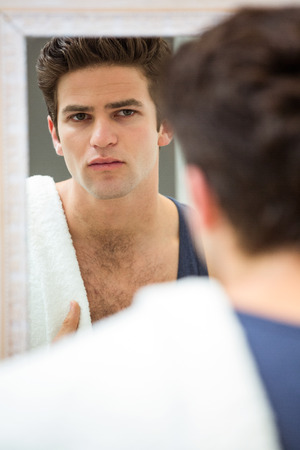 domicile: Man looking in mirror and checking his stubble in bathroom