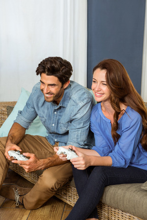 playing video game: Couple playing video game while sitting on sofa in living room