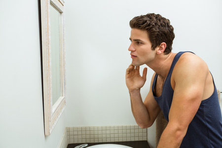 stubble: Reflection of young man in mirror checking his stubble in bathroom Stock Photo