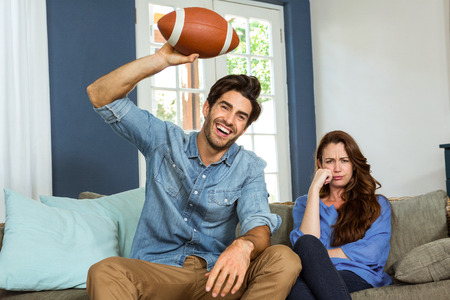 american: Couple in living room watching american football match on television