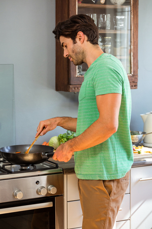 preparing food: Man preparing food in kitchen at home Stock Photo
