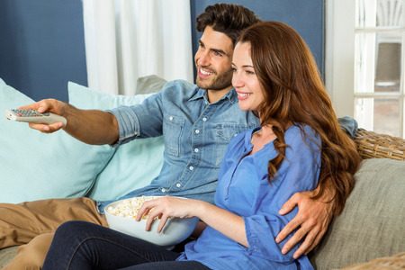 changing channel: Young couple having popcorn while watching television in living room Stock Photo