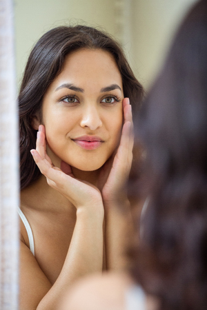 woman mirror: Young woman looking in mirror of bathroom at home