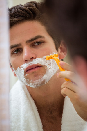 domiciles: Young man shaving in front of bathroom mirror